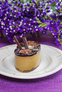 Cappuccino cake on white plate purple flowers in the background selective focus festive and party dessert Royalty Free Stock Photography