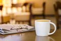 Cappuccino coffee cup on wooden table with newspaper Royalty Free Stock Photo