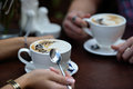 Cappuccino or latte coffee in white cup closeup of and woman hands girl on a break Royalty Free Stock Image
