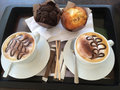 Cappuccino and muffins two cappuccinos two on a tray with sugars stir sticks silverware Royalty Free Stock Images