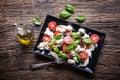 Caprese Salad.Mediterranean salad. Mozzarella cherry tomatoes basil and olive oil on old oak table. Italian cuisine