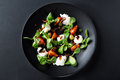 Caprese salad with mozzarella, tomato, basil and balsamic vinegar arranged on black plate and dark background. Top view Royalty Free Stock Photo
