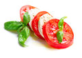 Caprese salad tomato and mozzarella slices with basil leaves Stock Photos