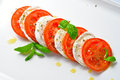 Caprese salad tomato and mozzarella slices with basil leaves Stock Photo