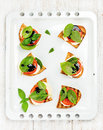 Caprese sandwiches with tomato, mozzarella cheese, basil and balsamic glaze on white baking tray over light wooden Royalty Free Stock Photo