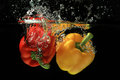 Capsicum fruit splash wate fresh red and yellow bell pepper gets hit by a water stream on black background water splashes conceptn Royalty Free Stock Photos