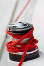 Capstan on the deck of sailing yacht with red rope Stock Photos