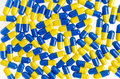 Capsule medical background, close up of pile of yellow blue tabl Royalty Free Stock Photo