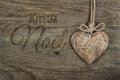 Caption in french joyeux noel in burnt letter script on wood with a heart wooden decoration ancient oak background and Royalty Free Stock Image