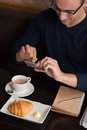 Capturing moment guy talking photo of fresh croissant and cup of coffee on his smartphone view from above Royalty Free Stock Image