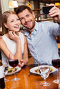 Capturing romantic moments beautiful young loving couple making selfie and smiling while sitting at the restaurant together Stock Images