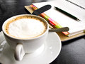 Capuchino coffee with notebook and pencil Royalty Free Stock Photos