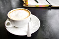 Capuchino coffee with notebook on a table Royalty Free Stock Photo