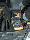 Car battery voltage checking auto mechanic measuring using multimeter Royalty Free Stock Image