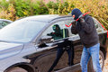 Car burglar in action a to rob something out of a Royalty Free Stock Images