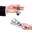 Car buying male hand holding a key and handing it over to another person woman holding dollars Stock Images
