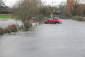 Car caught in flash flood a is on a country road as a swollen river breaks its banks england uk Stock Photography