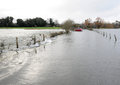 Car caught in flood a is on a country road as a swollen river breaks its banks and engulfs the road england uk Stock Image