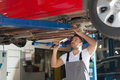 Car chassis inspection focused mechanic standing under holding lamp and checking a Royalty Free Stock Photo