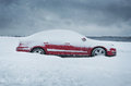 Car covered with the snow winter close up of red Royalty Free Stock Photo