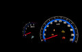 Car dashboard gauges illuminated at night. Royalty Free Stock Photography