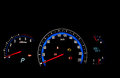Car dashboard gauges illuminated at night. Royalty Free Stock Image
