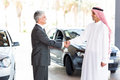 Car dealer arabian man smiling middle aged handshake with Royalty Free Stock Image