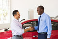 Car dealer handshake customer smiling african american with Stock Images