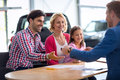 Car dealer selling new automobile to young family with child Royalty Free Stock Photo