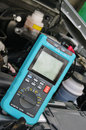 Car diagnostic tool against the background of the motor vehicle Royalty Free Stock Image