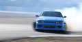Car drifting on a race track blue with lots of smoke Royalty Free Stock Photos