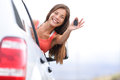 Car driver woman happy showing car keys out window new rental or driving licence concept with young female model on road trip Royalty Free Stock Images