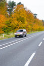 Car driving on country road autumn scene low angle motion blur Royalty Free Stock Image