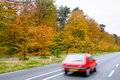 Car driving on country road autumn scene low angle motion blur Stock Photography