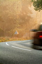 Car driving by on a forest road during fall Royalty Free Stock Images