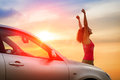 Car driving freedom and happiness female driver beside raising arms feeling the of towards the sunset woman vehicle on beautiful Stock Photo