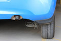 Car exhaust rear view of blue showing pipe and wheel Royalty Free Stock Photo