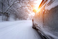 Car and falling snow in winter on forest road with much snow. Royalty Free Stock Photo