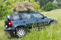Car at farm with hay meadow or field on roof farming concept Royalty Free Stock Photography