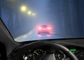 Car in fog driving a dark avenue thick seen through windscreen of other vehicle Stock Image