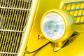 Car grille and headlight bright yellow vintage vehicle closeup Royalty Free Stock Photography