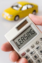 Car and  hand holding a pocket calculator with Leasing text Royalty Free Stock Photo