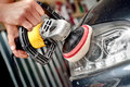 Car headlight cleaning with power buffer machine at service station Stock Photography