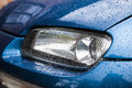 Car headlights after a rain with part of blue body are covered with water drops Royalty Free Stock Images
