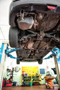 Car on a hoist or elevator to enable motor mechanic to access the underside during service repair and maintenance viewed Royalty Free Stock Images