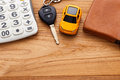 Car key with calculator on wood background Royalty Free Stock Photo