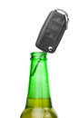 Car key in neck of bottle of bee - studio shot over white Royalty Free Stock Photo