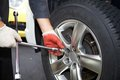 Car mechanic changing tire. Royalty Free Stock Photo