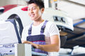 Car mechanic with diagnosis tool in Asian auto workshop Royalty Free Stock Photo