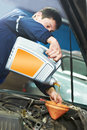 Car mechanic pouring oil into motor engine Royalty Free Stock Photo